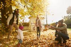 Familj som spelar med Autumn Leaves In Garden Together arkivbilder
