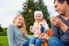 Familj som spelar med bubblor utomhus fotografering för bildbyråer