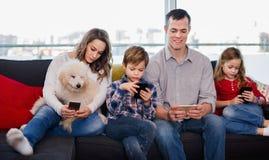 Familj som spelar med deras hemmastadda smartphones tillsammans Royaltyfri Bild