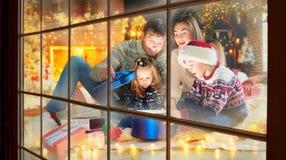 Familj som spelar med gåvor inomhus på juldagen arkivbilder