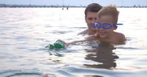 Familj som spelar med simningleksaken i havet stock video