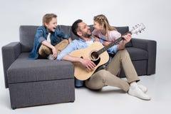Familj som spelar på gitarren och sjunger och att spendera tid tillsammans, medan sitta på soffan fotografering för bildbyråer