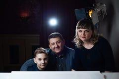 Familj som spelar på pianot Fadern och modern undervisar sonen att spela ett musikinstrument arkivbild