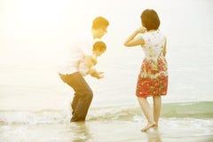 Familj som spelar på sjösidan Arkivbilder