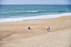 Familj som spelar på stranden på våren royaltyfria bilder