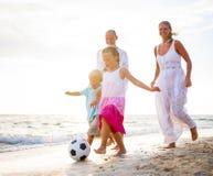 Familj som spelar på stranden Arkivbild