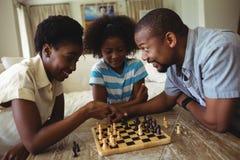 Familj som spelar schack tillsammans hemma i vardagsrummet Fotografering för Bildbyråer