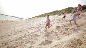 Familj som springer ner en sanddyn