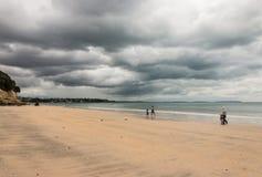 Familj som strosar på den Takapuna stranden Arkivfoton