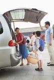 Familj som tar material ut från bilen som förbereder sig för picknick Royaltyfri Foto
