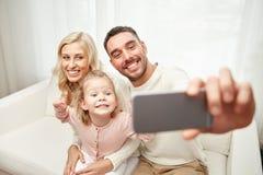 Familj som tar selfie med den hemmastadda smartphonen arkivfoton