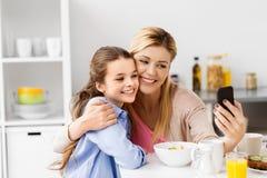 Familj som tar selfie vid smartphonen på frukosten royaltyfri foto