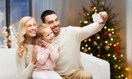 Familj som tar selfie vid smartphonen på jul arkivfoton
