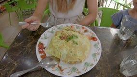 Familj som ?ter en traditionell malaysisk och indonesisk mat - nasigoreng som sl?s in i ett stekt ?gg Lopp till Malaysia och lager videofilmer
