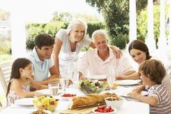 Familj som äter lunch utanför i trädgård Arkivfoton