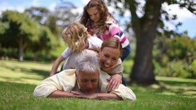 Familj som tillbaka ligger på fäder Royaltyfria Bilder