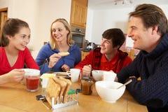 Familj som tillsammans äter frukosten i kök Arkivfoton