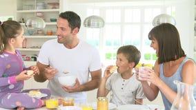 Familj som tillsammans äter frukosten i kök arkivfilmer