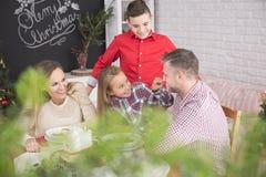 Familj som tillsammans äter julmål arkivfoto