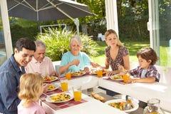 Familj som tillsammans äter lunch i sommar royaltyfria bilder