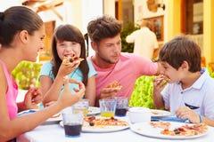 Familj som tillsammans äter mål på den utomhus- restaurangen royaltyfria bilder