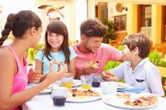 Familj som tillsammans äter mål på den utomhus- restaurangen arkivfoto