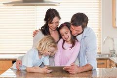 Familj som tillsammans använder en tabletdator Arkivbilder