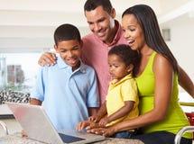 Familj som tillsammans använder bärbara datorn i kök Arkivbild