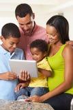 Familj som tillsammans använder den Digital minnestavlan i kök Arkivbilder