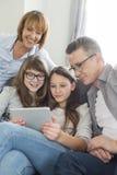Familj som tillsammans använder den digitala minnestavlan i vardagsrum Arkivbilder