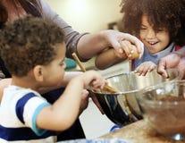Familj som tillsammans bakar i köket arkivbilder