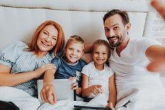 Familj som tillsammans gör det roliga fotoet i säng arkivbild
