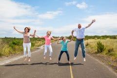 Familj som tillsammans hoppar på vägen Arkivbild