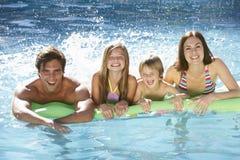 Familj som tillsammans kopplar av i simbassäng Arkivbild