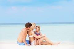 Familj som tillsammans kopplar av på den härliga stranden Arkivbild