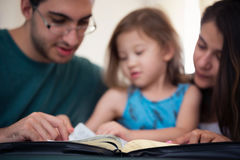 Familj som tillsammans läser bibeln arkivbilder