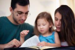 Familj som tillsammans läser bibeln royaltyfri foto