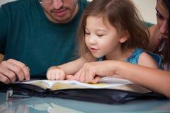Familj som tillsammans läser bibeln royaltyfri fotografi