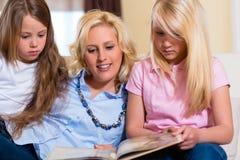 Familj som tillsammans läser en bok royaltyfri bild