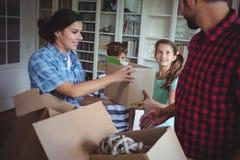 Familj som tillsammans packar upp lådor Arkivbild