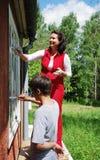 Familj som tillsammans reparerar huset på yttersidan Arkivfoton