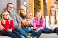 Familj som tillsammans sitter på soffan Arkivfoton