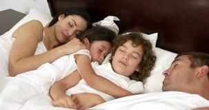 Familj som tillsammans sover på säng stock video