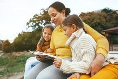 Familj som tillsammans spenderar tid vid sjön Arkivfoto