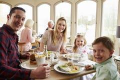 Familj som tillsammans tycker om mål i restaurang royaltyfria foton