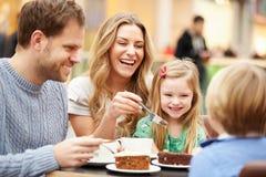 Familj som tillsammans tycker om mellanmålet i kafé Royaltyfri Foto