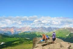 Familj som tillsammans tycker om tid på överst av berget Fotografering för Bildbyråer