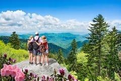Familj som tillsammans tycker om tid på att fotvandra tur i bergen arkivbilder