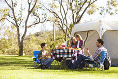 Familj som tycker om campa ferie i bygd arkivfoto