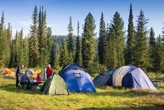 Familj som tycker om campa ferie i bygd Fotografering för Bildbyråer